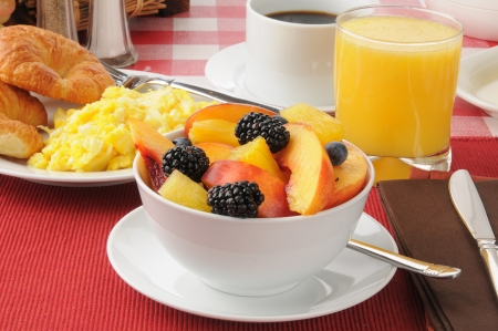 A bowl of fresh fruit with scrambled eggs and croissants