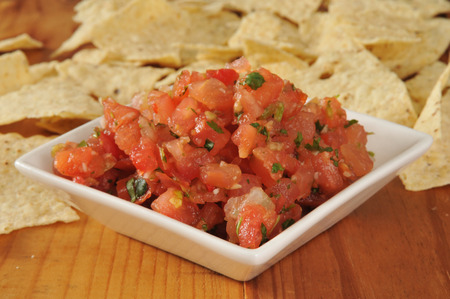 A small dish of Pico de Gallow with corn tortilla chips in the background
