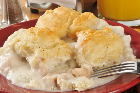 chicken and gravy on a bed of mashed potatoes, topped with golden flakey biscuits