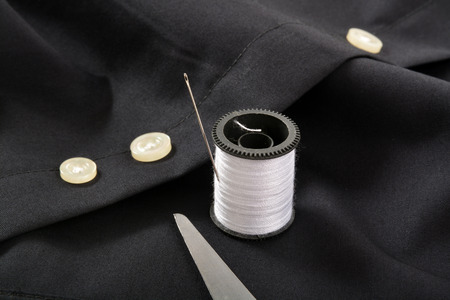 The tip of scissors with a needle and thread by the spare button on a shirt tail