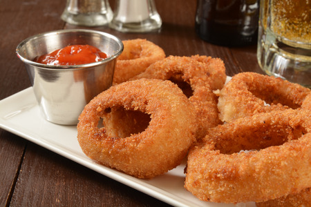 A plate of onion rings on a bar counter with a mug of beer