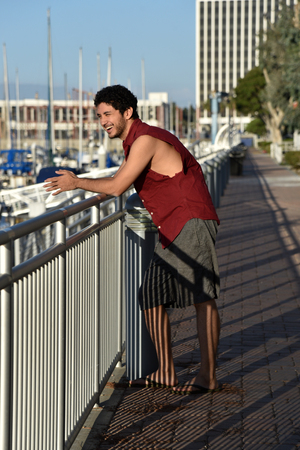 A happy multi-ethnic young man looking out over the marina