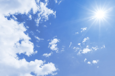 A blue sky with sun and clouds background