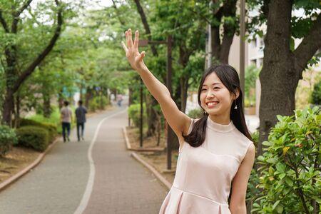 Photo pour Young woman waving hand to someone - image libre de droit