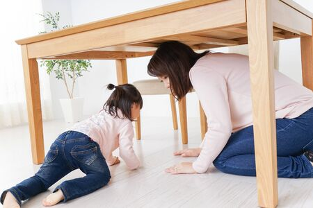 Photo pour A parent and child huddling under a table - image libre de droit