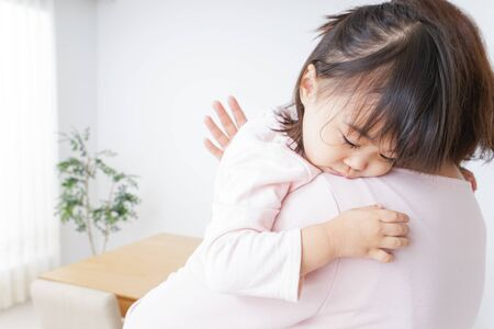 Photo for Sleeping child carried by mother - Royalty Free Image
