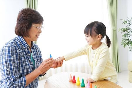 Photo pour Child playing a game with grandmother - image libre de droit