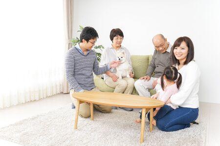 Photo pour Three-generation family taking care of dog - image libre de droit