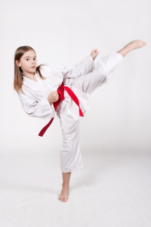 Karate young girl in a kimono with a red belt kicking up, isolated on white background