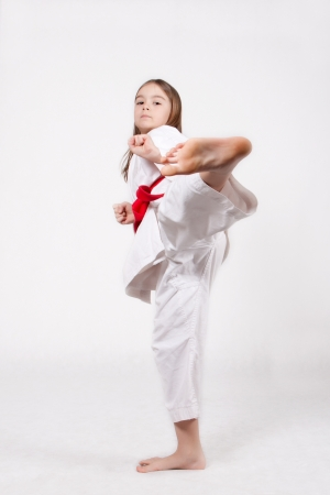 Karate young girl in a kimono with a red belt kicking up, isolated on white backgroundの写真素材
