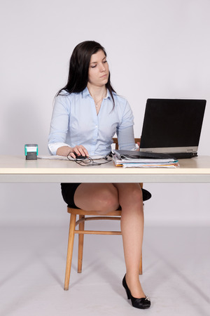 Young woman working behind a desk clerk at the laptop, with one foot on a chair
