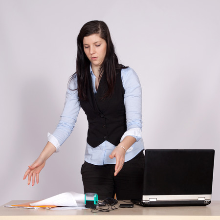 Young female boss at table with laptop throwing papers on the table, and upsets