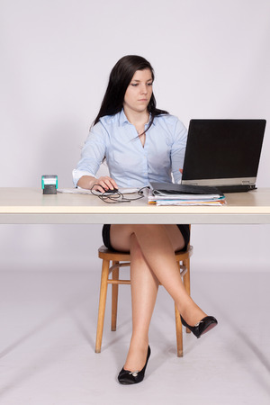 Young woman working behind a desk clerk at the a laptop with legs crossed