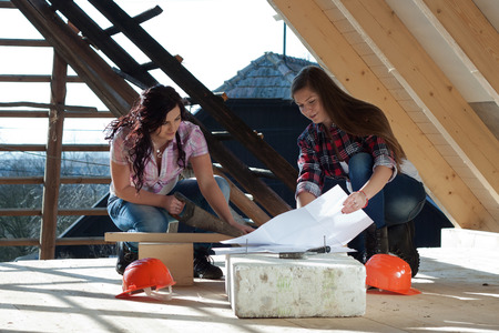 Two young long-haired woman sawed wood for the roof of the house in accordance with drawing