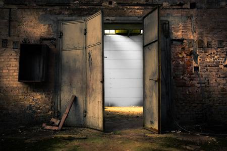 Old rusty metal door in an abandoned warehouse