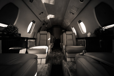 a luxury aircraft interior, leather seats, black and white