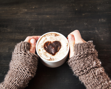 Photo pour Hands Holding Warm Cappuccino with Froth and Cocoa Heart Shape - image libre de droit