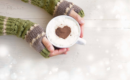 Holding Coffee Latte Cup with Cocoa Shape and Cozy Wool Hands Warmers on Magic Winter Background