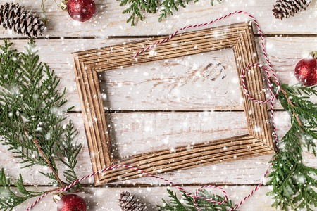 Photo pour Christmas decoration on the white wooden background. Christmas interior with photo frame, decorative branches, presents on wooden table. New Year winter composition. Top View. Space for text - image libre de droit