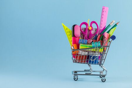 Photo pour Shopping cart with different stationery on the blue background. - image libre de droit