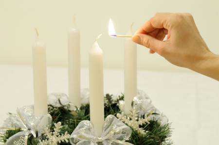 Christmas advent wreath on table - hand is going to light first candle