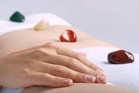 Alternative medicine - healing by semiprecious gems placed on body chakras, shallow depth of field