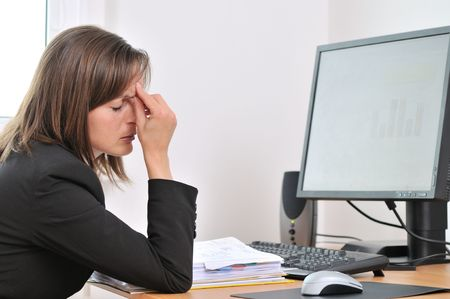 Young business woman with headache and tired closed eyes sitting at computer in workplace