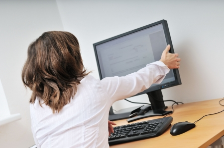Business person (young woman) adjusting computer monitor - office interior