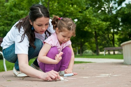 Mother is teaching her cute daughter to draw with chalk on sidewalk