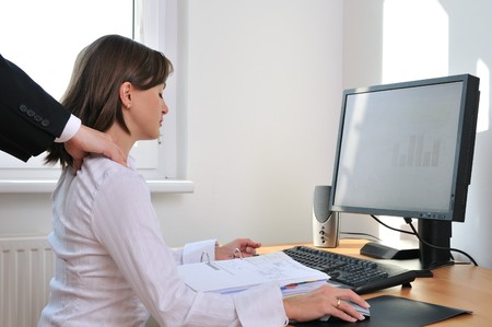 Business working person (woman) behind computer receiving neck massage from colleague (only hands visible)
