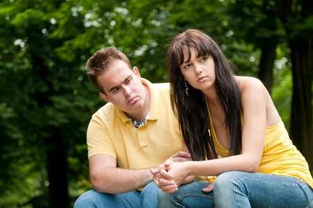 Young couple sitting outdoors on bench having relationship problems