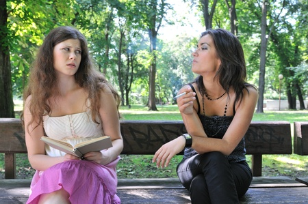 Two young people outdoors on bench in park, one teenager smoking cigarette annoys another girl