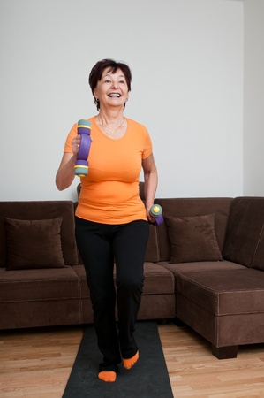 Smiling mature fitness woman excercising with barbells at home - walking