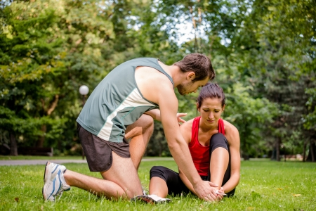 Sport injury - young fitness woman holding her ankle  with pain, man is helping