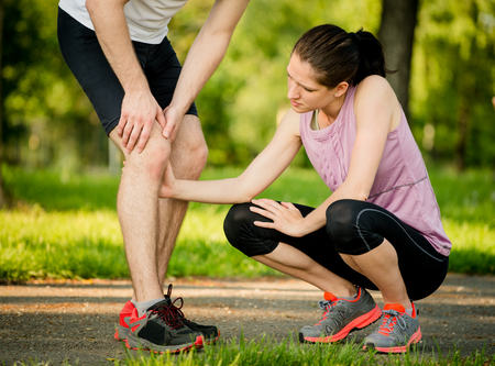 Woman helps to man with injured knee at sport activity