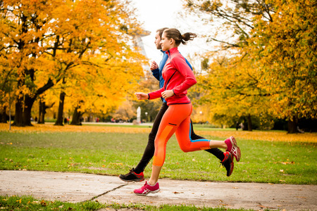 Photo pour Couple jogging in autumn nature - image libre de droit