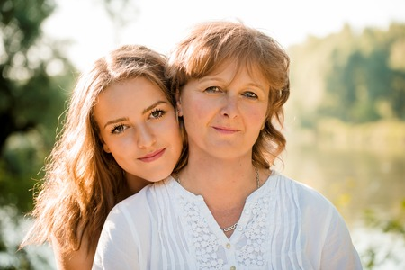 Photo pour Outdoor portrait of mature mother with her teenage daughter - backlit with sun - image libre de droit