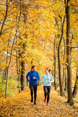 Photo pour Young couple talking while jogging together in beautiful autumn nature - image libre de droit