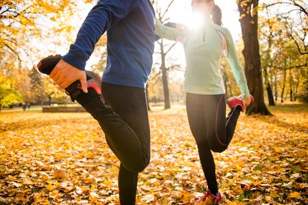 Foto de Detail of man and woman stretching legs before jogging in autumn nature - Imagen libre de derechos