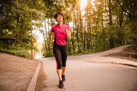 Vital senior woman jogging in park at sunset