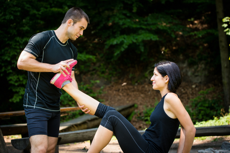 Man stretches womans leg - muscle spasm after sport training