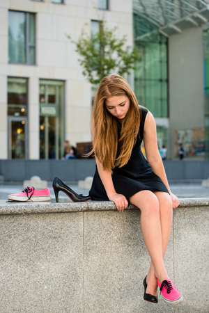 Which shoes to choose - young woman on street one foot in sneaker and other in high heel