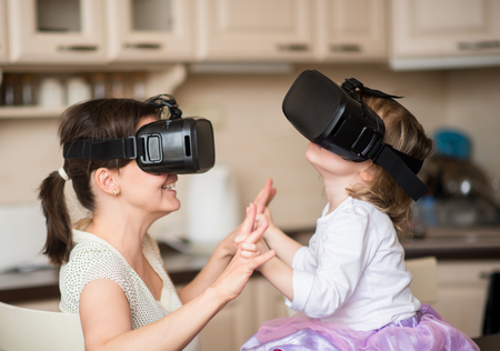 Photo pour Mother and child playing together with virtual reality headsets indoors at home - image libre de droit