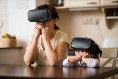 Photo pour Mother and child together with virtual reality headsets indoors at home - image libre de droit