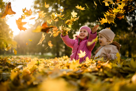 Photo pour Kids having fun in park, throwing up leaves. - image libre de droit