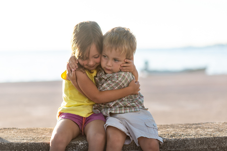 Photo for Brother and sister sitting at lake front embracing - Royalty Free Image