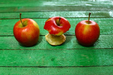 Three apples on green wooden boards