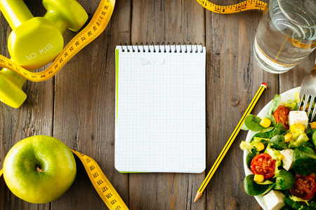 Workout and fitness dieting copy space diary  Healthy lifestyle concept  Salad, apple, dumbbell, water and measuring tape on rustic wooden table