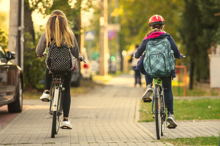 Photo for Two Girls Riding a Bicycle - Royalty Free Image
