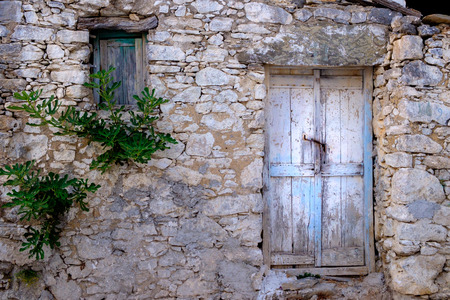 Old wooden door and window in stone wall in vintage style, Greece